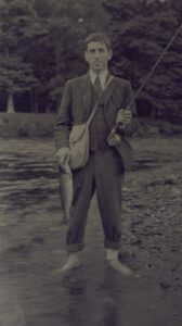 Black-and-white image of Stephen O'Mara, holding a fish and fishing rod
