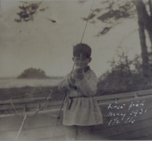 Black-and-white photo of Peter O'Mara as a child, holding a fish