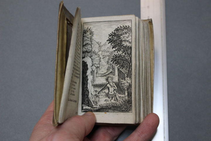 small book held open to show a black and white engraving of a man in a river in an idyllic landscape