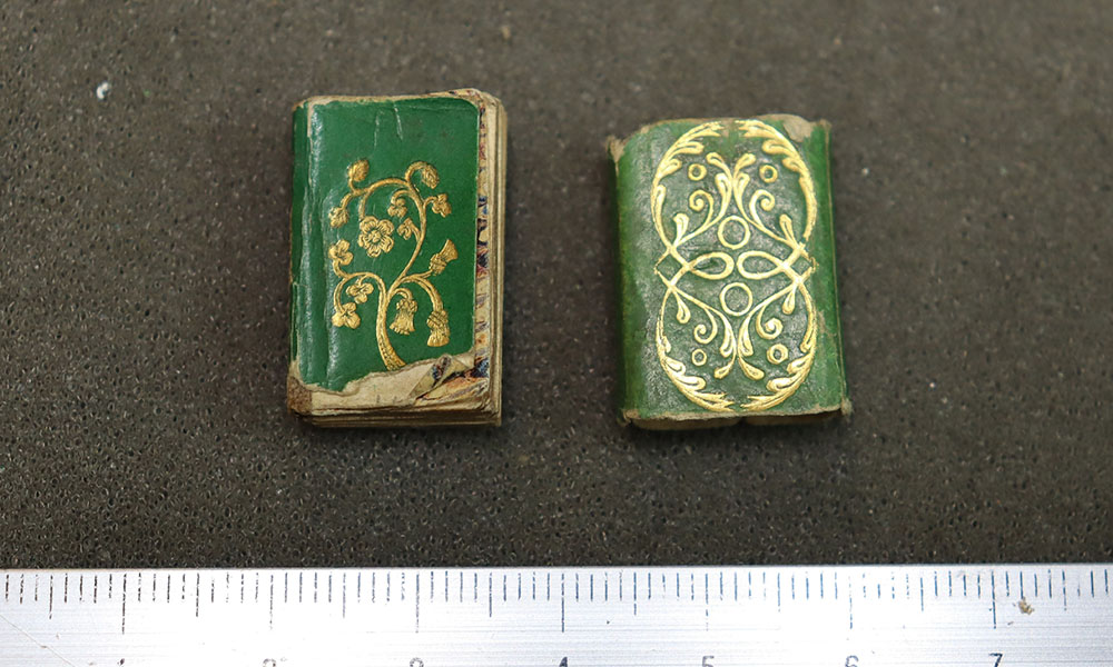 Minature book and paper case on grey background. The book and slipcase are green with gold decorations.
