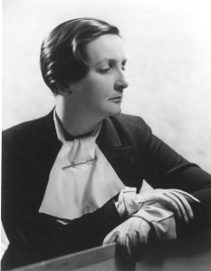 black-and-white portrait of seated Kate O'Brien in profile with large white tie and gloves