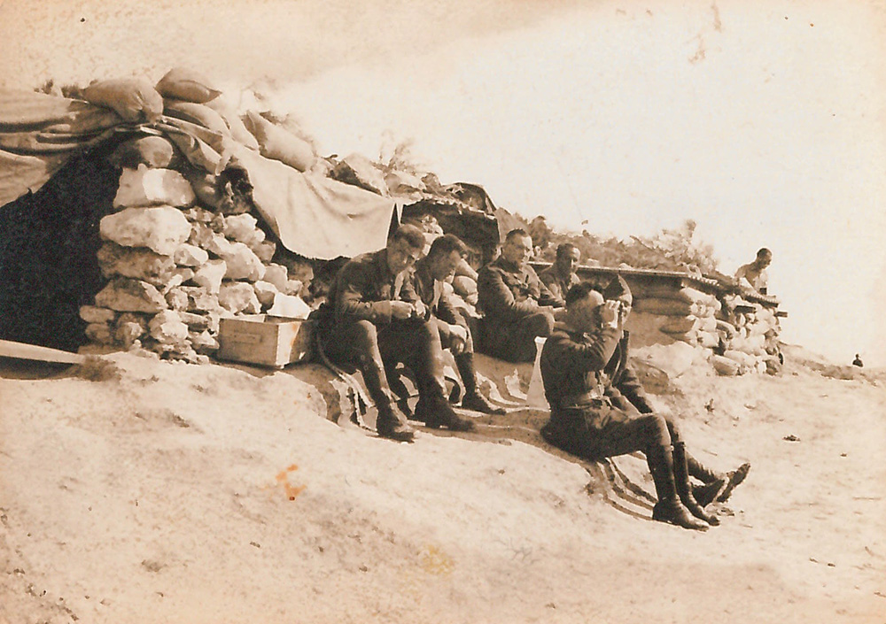 black-and-white picture of seated men in military uniforms, one looking through binoculars, in front of stacked sandbags
