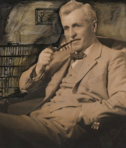 black-and-white portrait of seated Marucie Walsh in formal attire smoking a pipe, artwork of bookshelves in the background