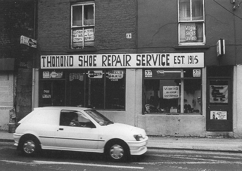 black-and-white picture of a streetscape with a white car, passing the shop front of Michael Healy's home and shoe repair shop