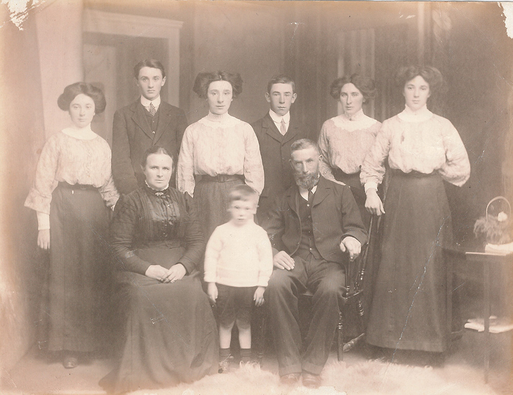 black-and-white family picture of the Noonan family in formal attire, including four girls and three boys. The parents seated in the front row and Thomas Noonan standing in the back row