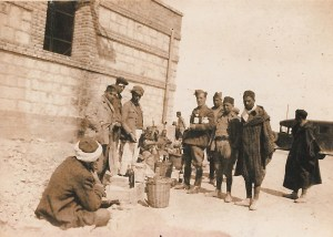 black-and-white picture of a group of Irish Brigade volunteers in military and civilians in moorish clothes, with baskets holding bottles of wine