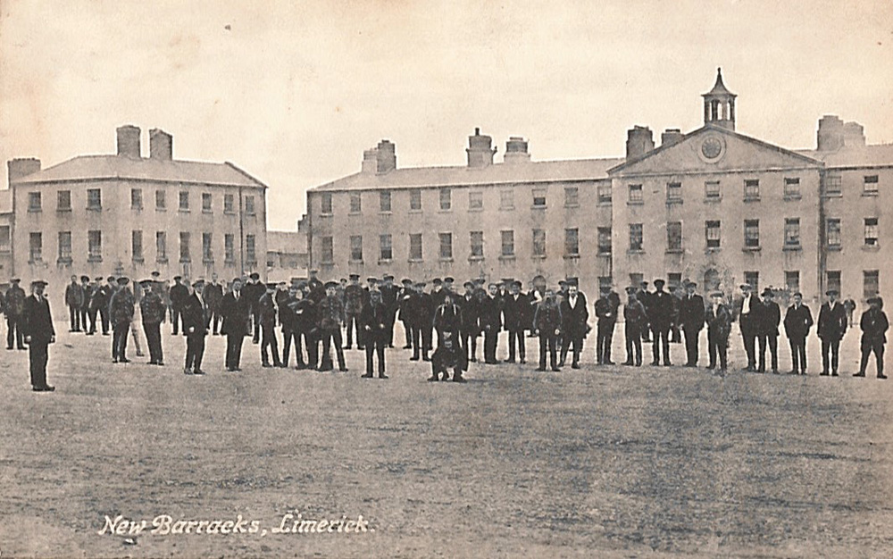 black-and-white postcard of a large group of standing men in front of Limerick Barracks