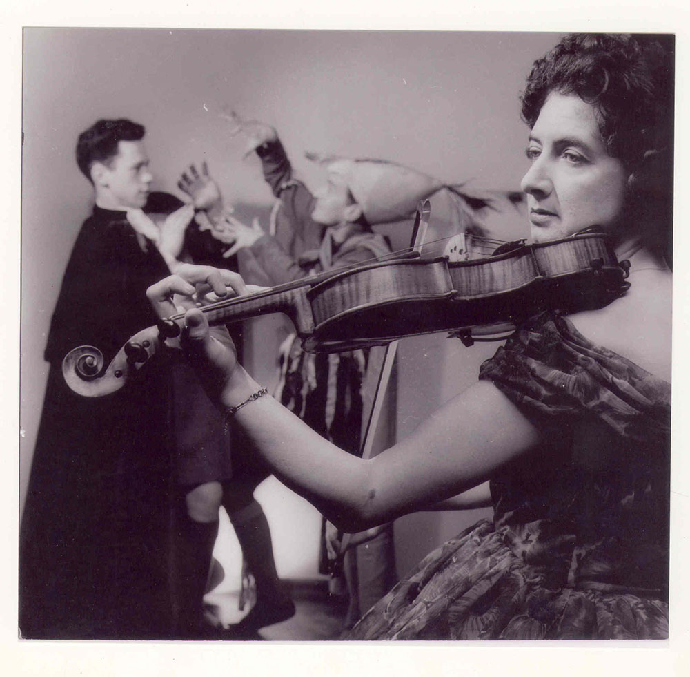 black-and-white picture of Patricia Mulholland, holding a violin, John Garvin and Hugh Murray in the background, in a scene from The Black Rogue