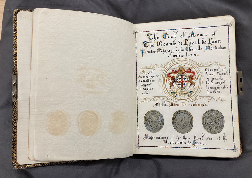Opened notebook relating to the de Laval family, featuring handwriting, ornaments and coat of arms