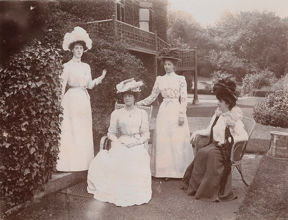 black-and-white picture of four ladies posing with hats in a garden, from an album compiled by May, Countess of Limerick