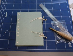 A book with soft cover made from paper and white ties at the foredge.