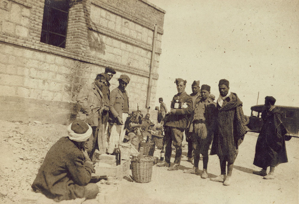 Photograph of Irish soldiers buying wine on the street from the Moors.