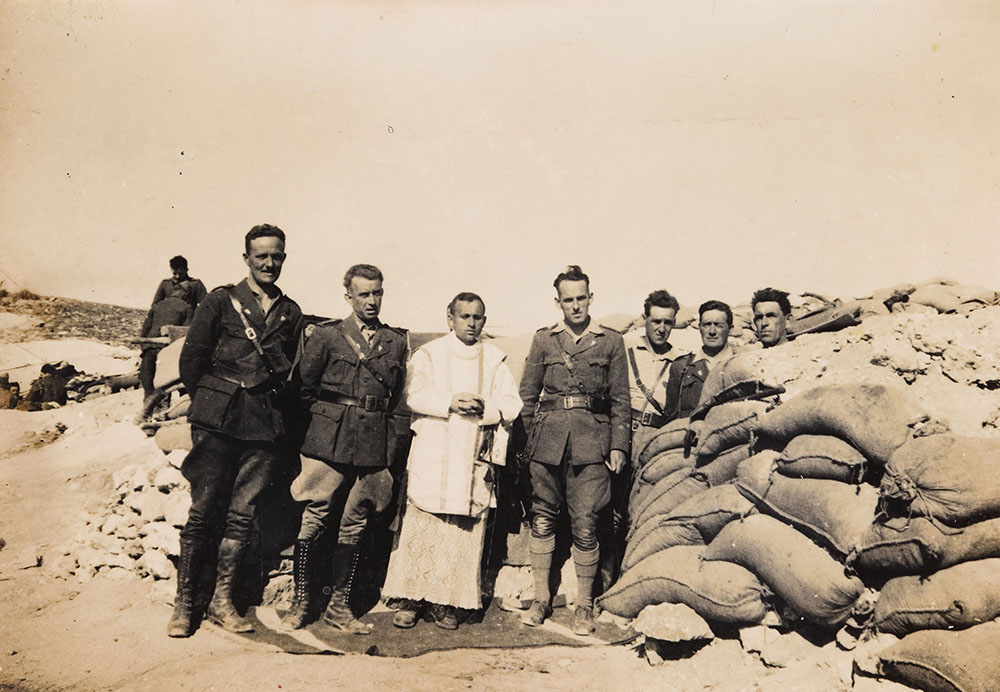 Photograph of Padre Alonso standing with Irish officers in the trenches.