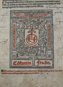photograph of a printed image. The print is black and red, it has a square frame of two pillars holding up a decorated cross beam, with decorative elements in red, underneath is a banner with the text Constantin Fradin. Inside of the square, there is a mermaid and a knight in armour holding a shield with the initials CF between them, with a tree in the background. The mermaid's tail is rising from a fountain spouting water, and surrounding the tree are red strawberries.